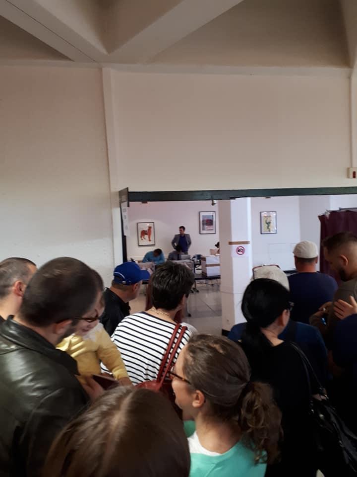 """(Foto) Viață de român la vot în Diaspora. Ciprian Mihali: """"Mâncăm ce apucăm, magazinele din preajma ambasadei s-au golit, oamenii împart cu cei din preajma lor apă, fructe, biscuiți. Picioarele ne ustură îngrozitor, dar nu ne lăsăm. Doar bateriile la telefon cedează. Oamenii aceștia ..."""" 3"""